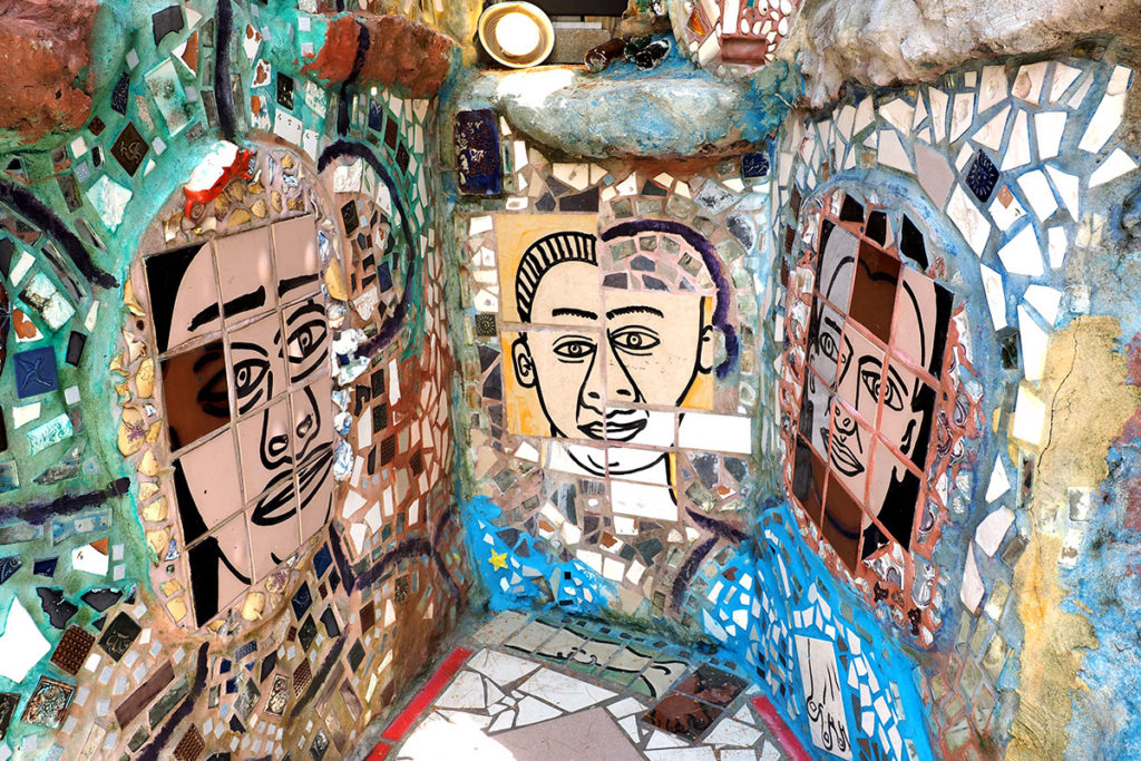 A grotto of abstract human faces executed in ceramic tiles
