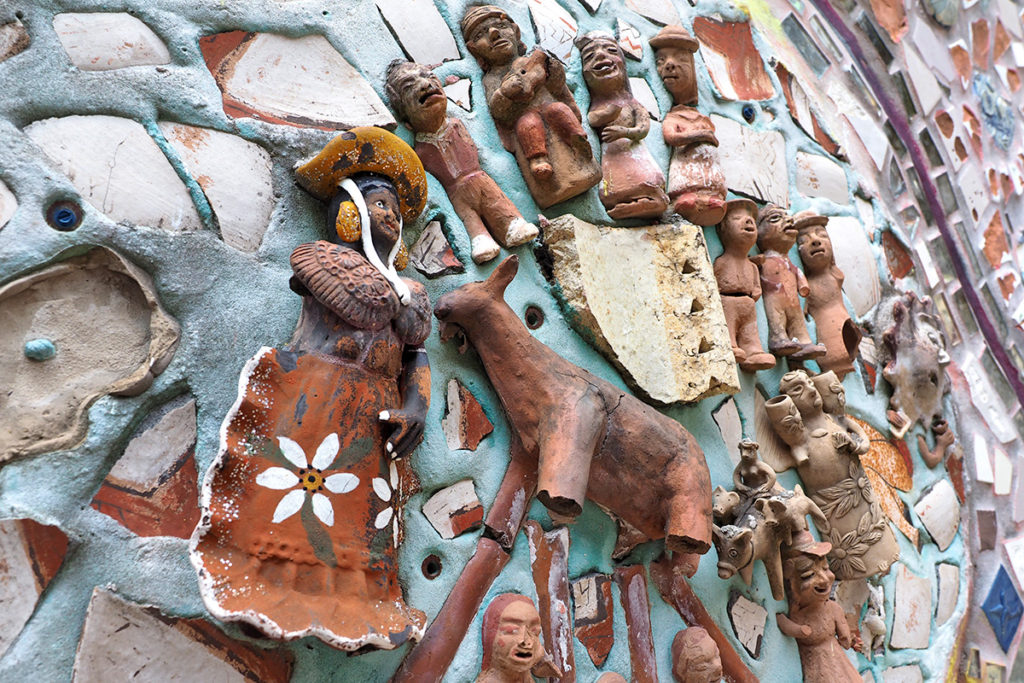 Folk art objects from South America are embedded in the walls