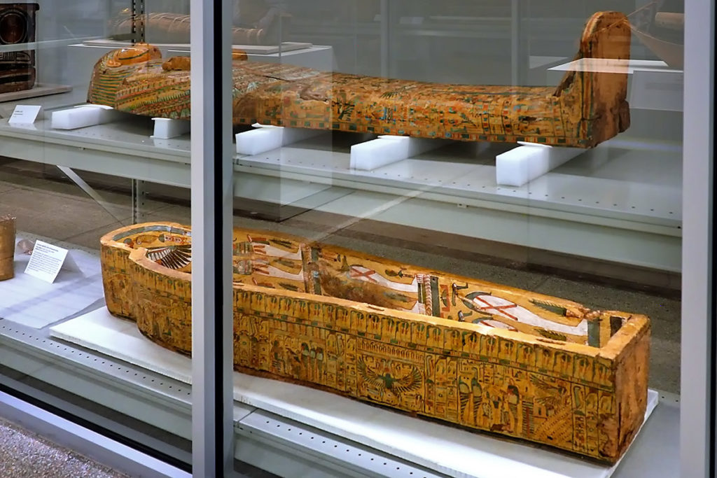 Intricately painted, bright yellow Egyptian coffin lid.