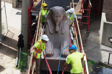 Engineers guide the massive sphinx in its move.