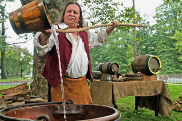 Beer historian Richard Wagner pours water from a wooden bucket.