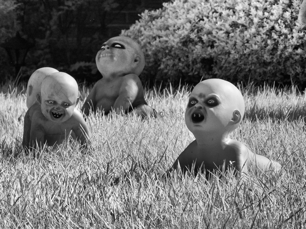 Monster babies with fangs crawl across a Halloween lawn display