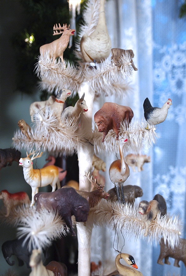 Antique celluloid Christmas toys festoon a feathered Christmas tree