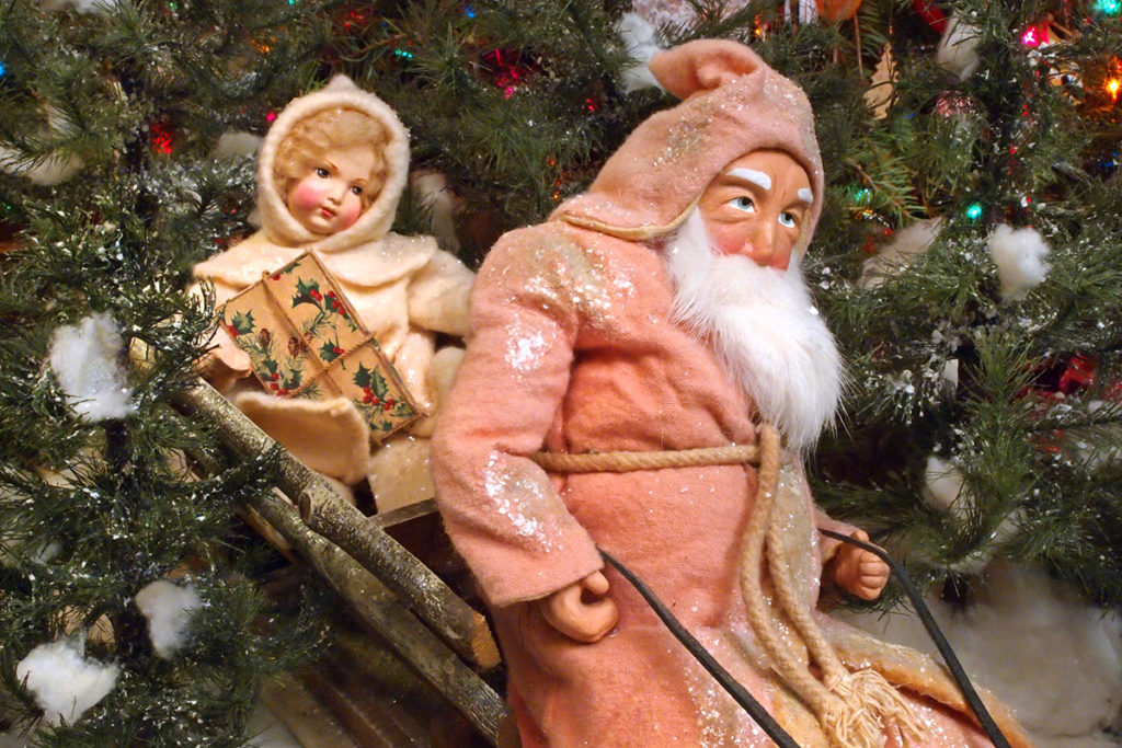 Santa figure in an antique wooden wagon decked out as a sleigh