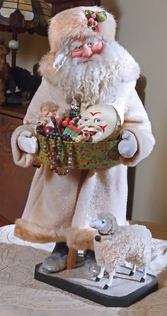 A custom-made Carpenter Santa figure with a basket of Christmas toys.