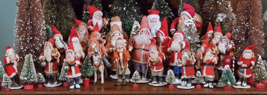 A collection of miniature antique Santa Clause figures from around the world