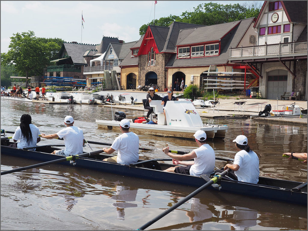 Rowers pass the Schuylkill River boathouse of the University of Pennsylvania.