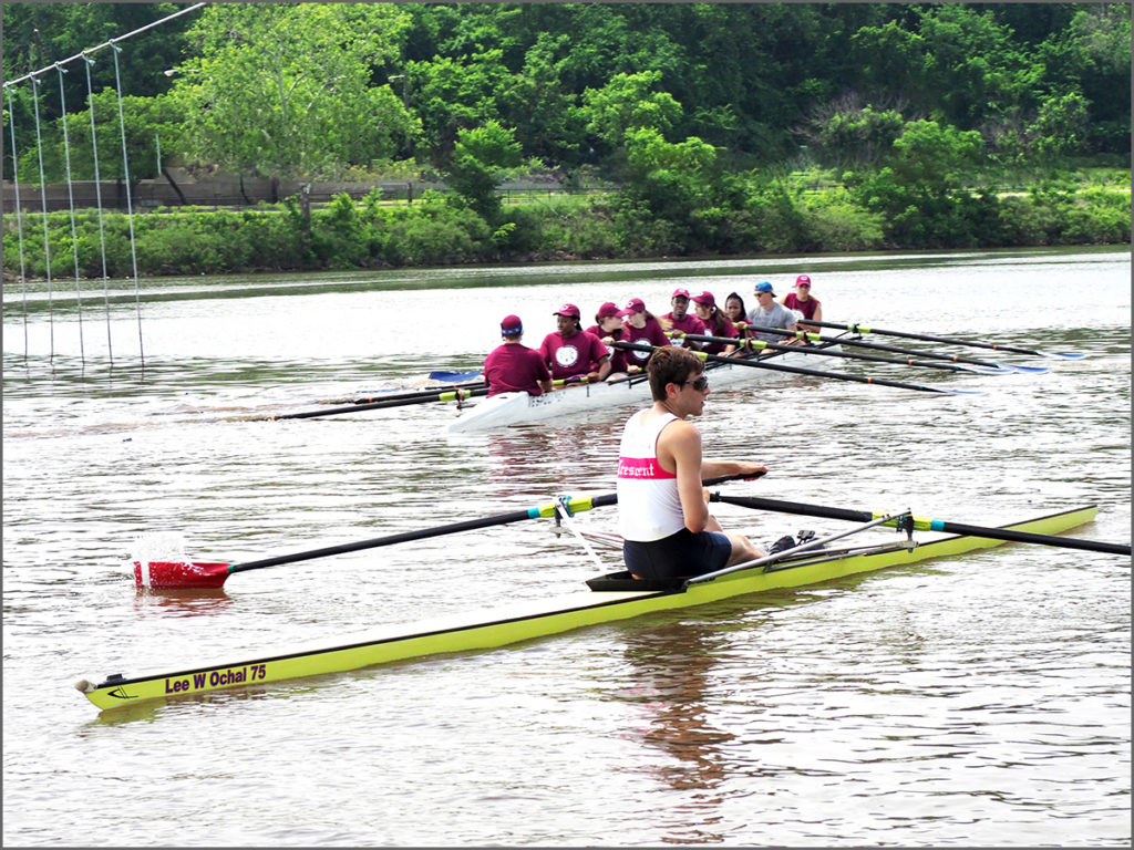A single scull next to a nine-man racing shell.