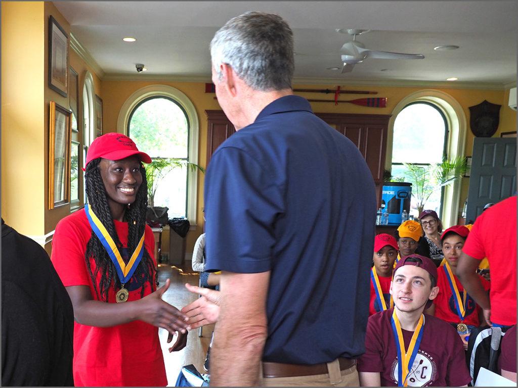 Rowing coach Dan Lyons congratulates Aminata Jalloh on her team's win.