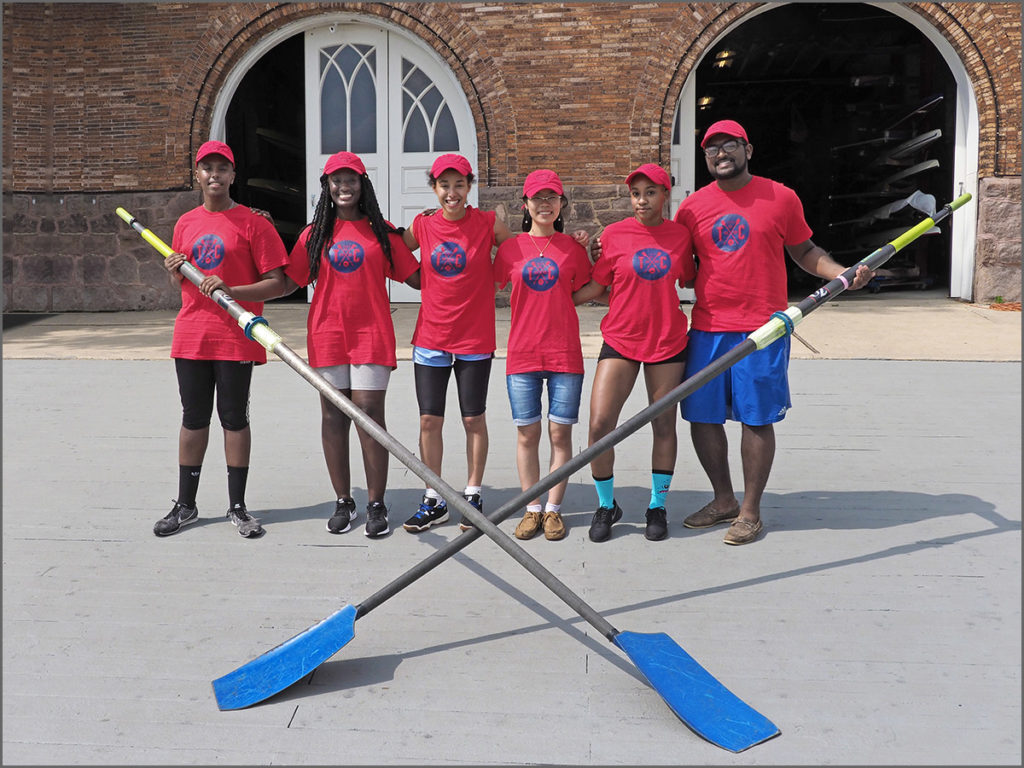 Rowing student enjoy a photo op with their crossed oars.