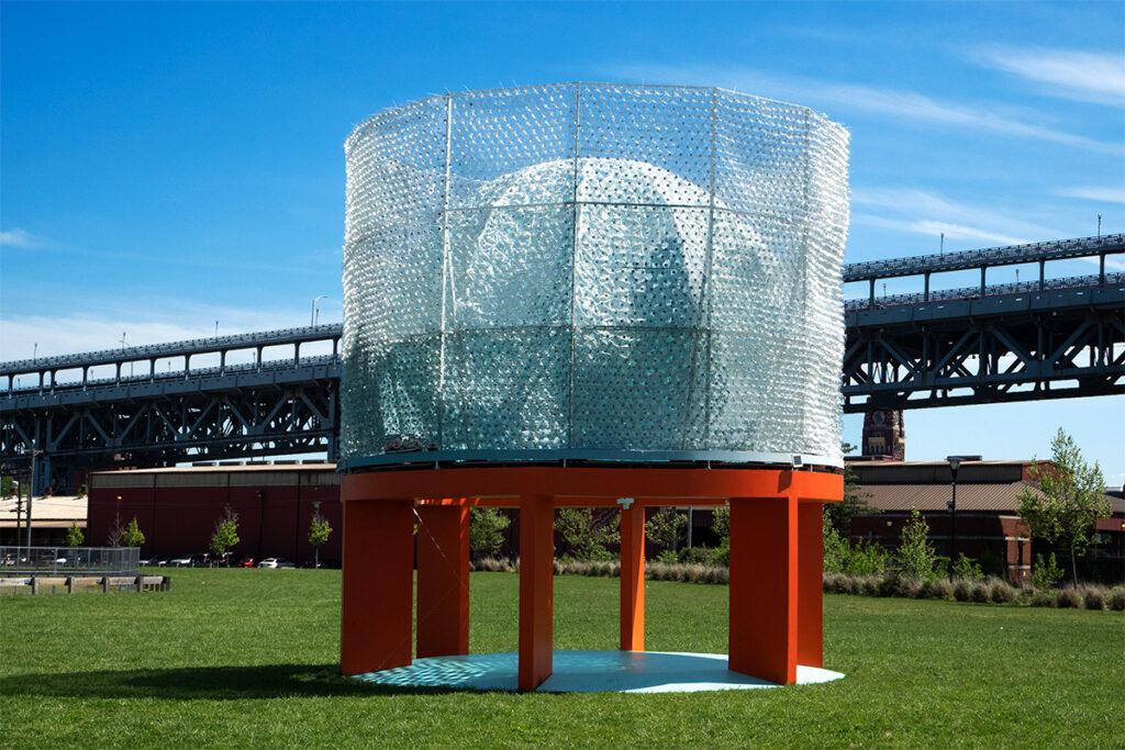 Powered by plastic bottle scoops that catch the wind, the Turntable sculpture sits next to the Ben Franklin Bridge.